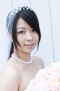ブーケを持ち微笑む花嫁の写真素材 [FYI04556774]