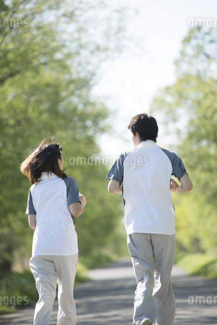ジョギングをするカップルの後姿の写真素材 [FYI04556797]