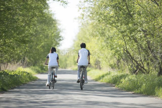 自転車に乗るカップルの後姿の写真素材 [FYI04556827]