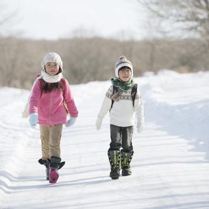 雪道を歩く小学生の写真素材 [FYI04556844]
