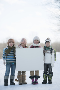 雪道でメッセージボードを持つ小学生の写真素材 [FYI04556847]