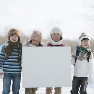 雪道でメッセージボードを持つ小学生の写真素材 [FYI04556854]