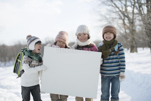 雪道でメッセージボードを持つ小学生の写真素材 [FYI04556855]