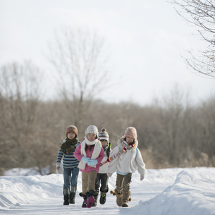 雪道を歩く小学生の写真素材 [FYI04556857]