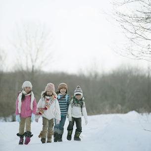 雪道を歩く小学生の写真素材 [FYI04556863]