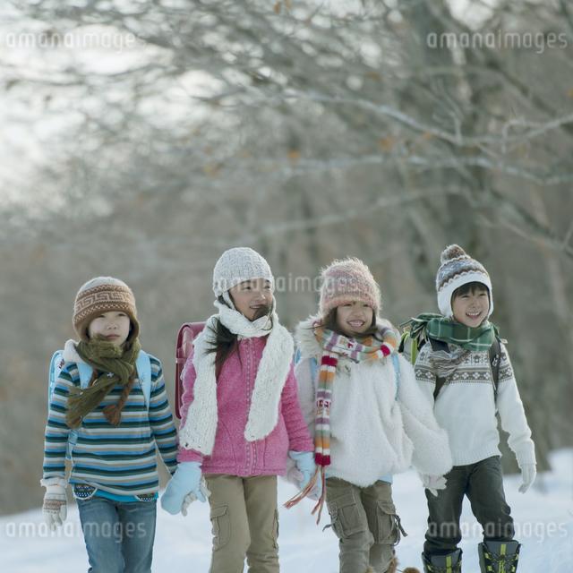 雪道を歩く小学生の写真素材 [FYI04556870]