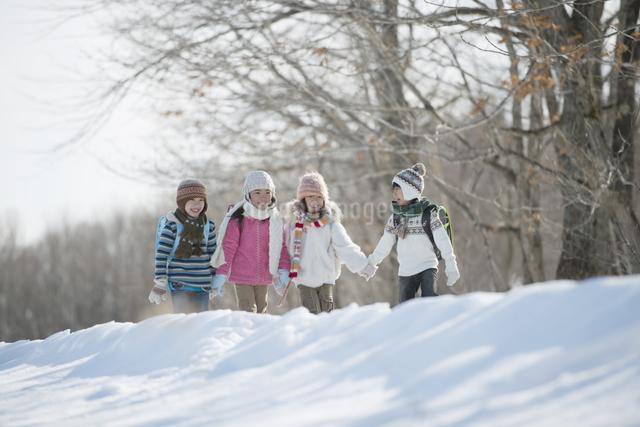 雪道を歩く小学生の写真素材 [FYI04556880]