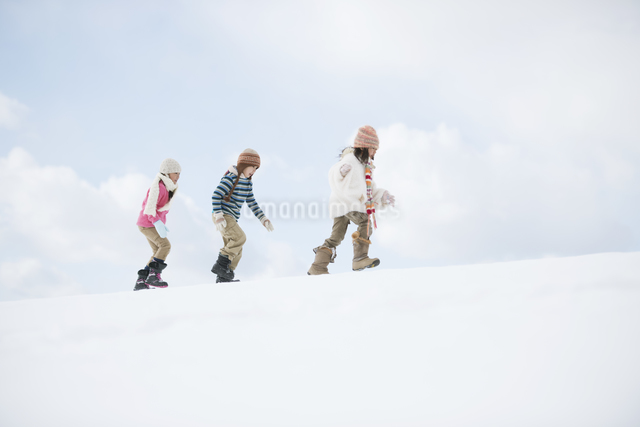 雪原を歩く小学生の写真素材 [FYI04556885]