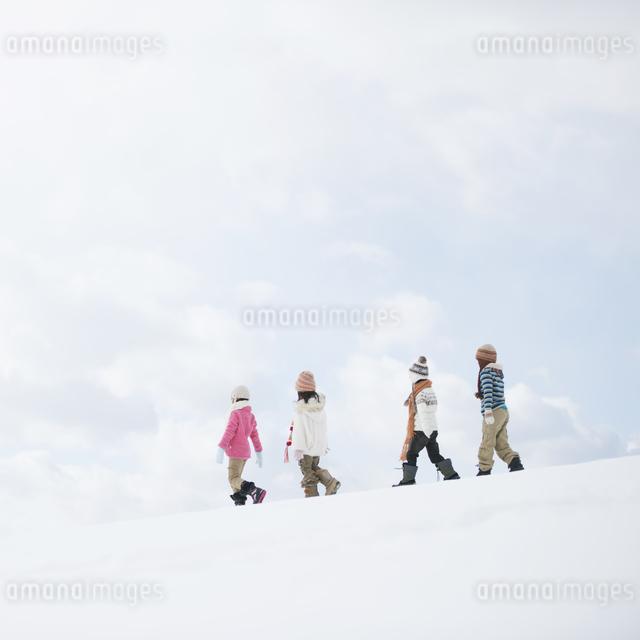 雪原を歩く小学生の写真素材 [FYI04556887]