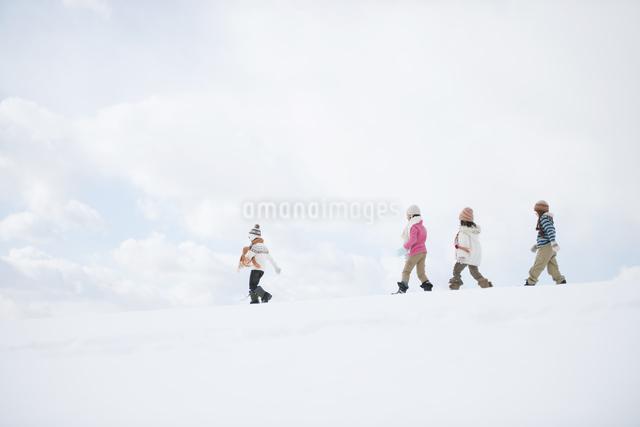 雪原を歩く小学生の写真素材 [FYI04556893]
