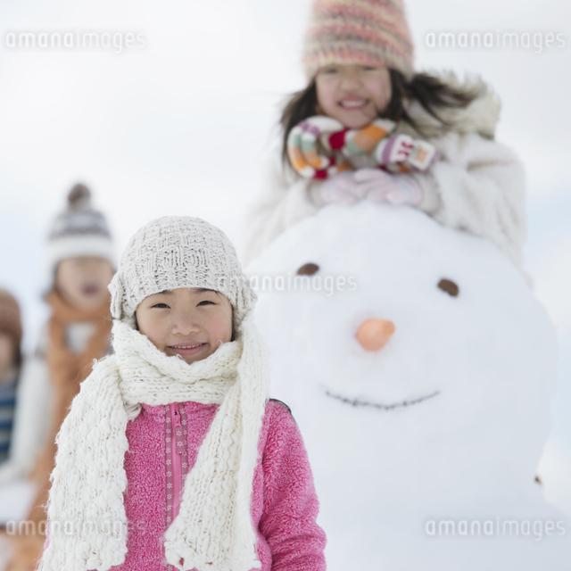 雪だるまの周りで微笑む小学生の写真素材 [FYI04556901]