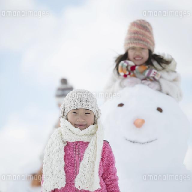雪だるまの周りで微笑む小学生の写真素材 [FYI04556903]