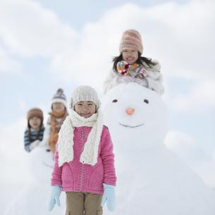 雪だるまの周りで微笑む小学生の写真素材 [FYI04556905]