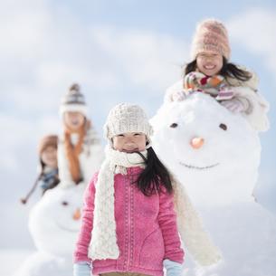 雪だるまの周りで微笑む小学生の写真素材 [FYI04556907]