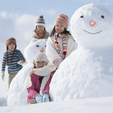 雪だるまの周りで微笑む小学生の写真素材 [FYI04556928]