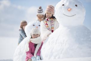 雪だるまの周りで微笑む小学生の写真素材 [FYI04556931]