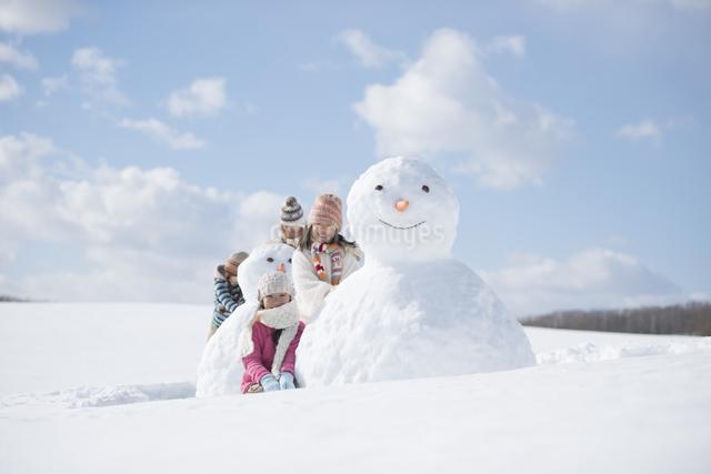 雪だるまの周りで微笑む小学生の写真素材 [FYI04556932]