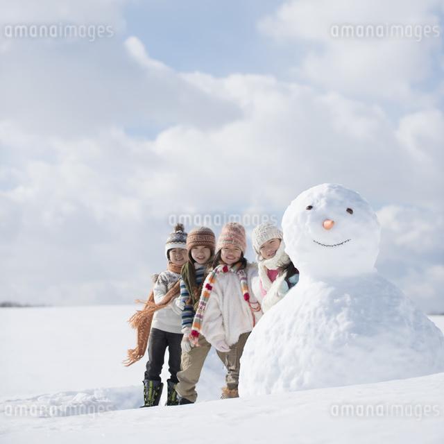 雪だるまの周りで微笑む小学生の写真素材 [FYI04556940]