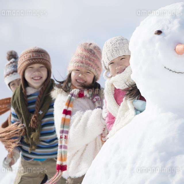 雪だるまの周りで微笑む小学生の写真素材 [FYI04556944]