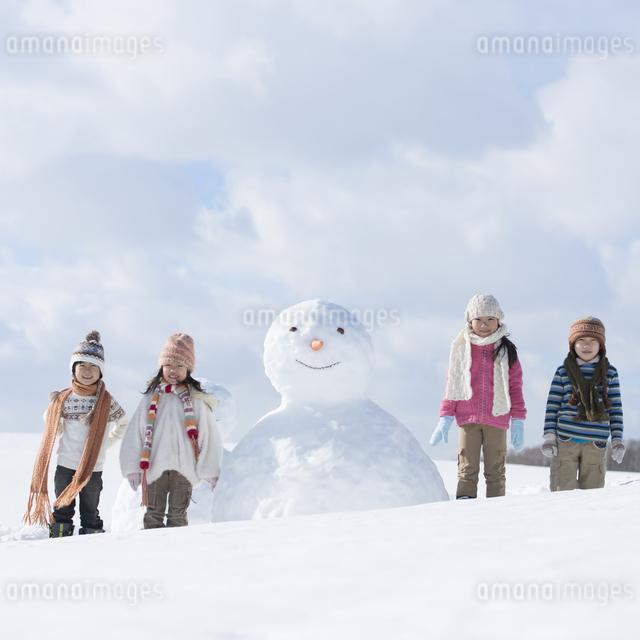 雪だるまの周りで微笑む小学生の写真素材 [FYI04556950]
