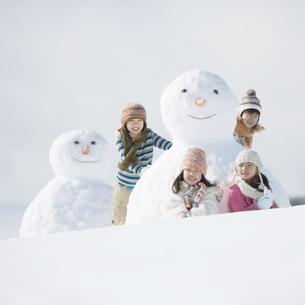雪だるまの周りで微笑む小学生の写真素材 [FYI04556956]