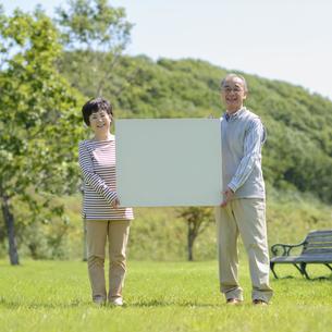 メッセージボードを持つシニア夫婦の写真素材 [FYI04557075]