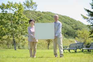 メッセージボードを持つシニア夫婦の写真素材 [FYI04557077]