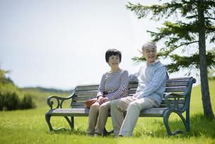 ベンチに座り微笑むシニア夫婦の写真素材 [FYI04557131]