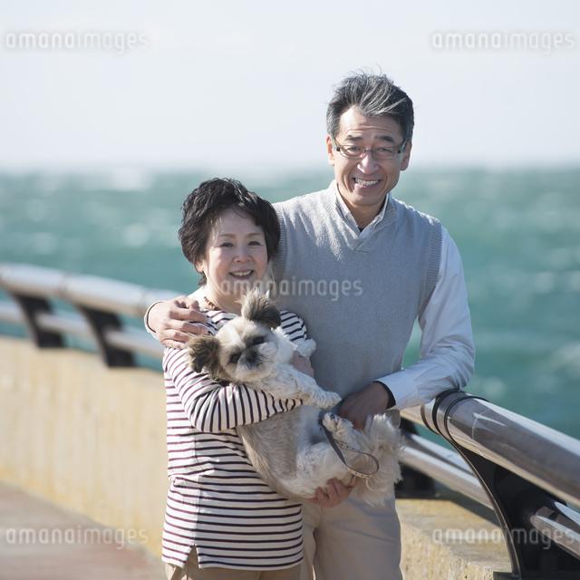 犬を抱き微笑むシニア夫婦の写真素材 [FYI04557141]