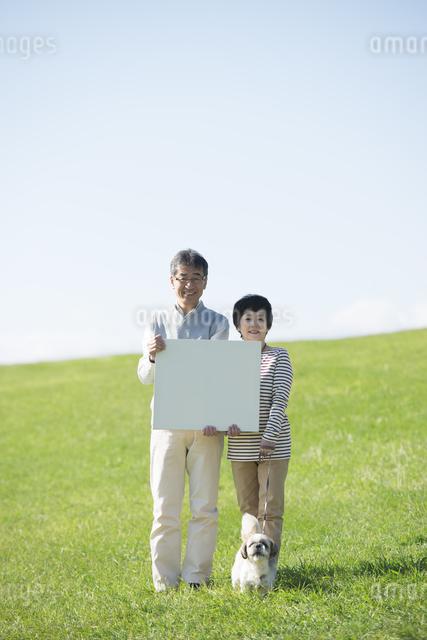 草原でメッセージボードを持つシニア夫婦と犬の写真素材 [FYI04557149]