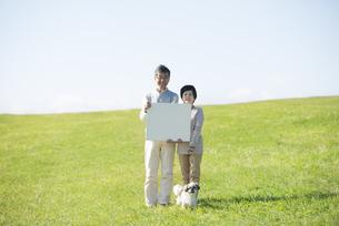 草原でメッセージボードを持つシニア夫婦と犬の写真素材 [FYI04557150]