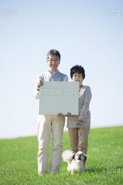 草原でメッセージボードを持つシニア夫婦と犬の写真素材 [FYI04557151]