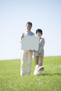 草原でメッセージボードを持つシニア夫婦と犬の写真素材 [FYI04557152]