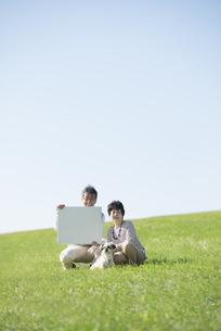 草原でメッセージボードを持つシニア夫婦と犬の写真素材 [FYI04557156]