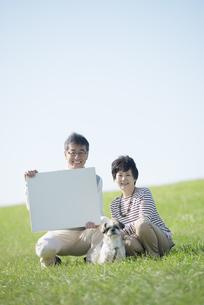 草原でメッセージボードを持つシニア夫婦と犬の写真素材 [FYI04557157]