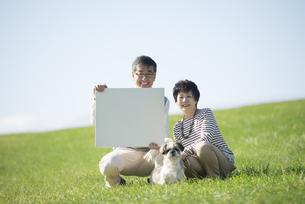 草原でメッセージボードを持つシニア夫婦と犬の写真素材 [FYI04557158]