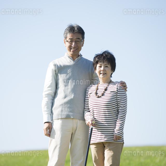 草原で微笑むシニア夫婦の写真素材 [FYI04557161]