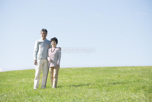草原で微笑むシニア夫婦の写真素材 [FYI04557162]