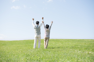 草原で両手を挙げるシニア夫婦の後姿の写真素材 [FYI04557166]