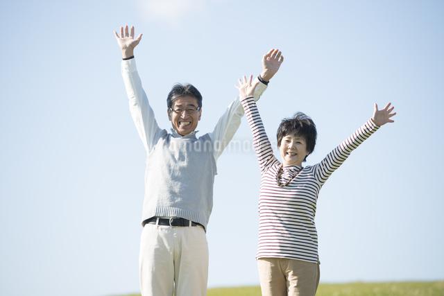 草原で両手を挙げるシニア夫婦の写真素材 [FYI04557169]