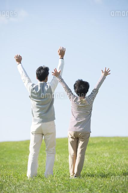 草原で両手を挙げるシニア夫婦の後姿の写真素材 [FYI04557171]