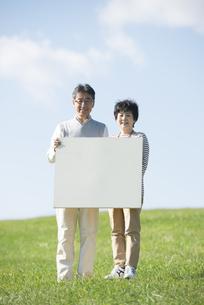草原でメッセージボードを持つシニア夫婦の写真素材 [FYI04557183]