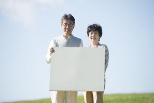 草原でメッセージボードを持つシニア夫婦の写真素材 [FYI04557184]