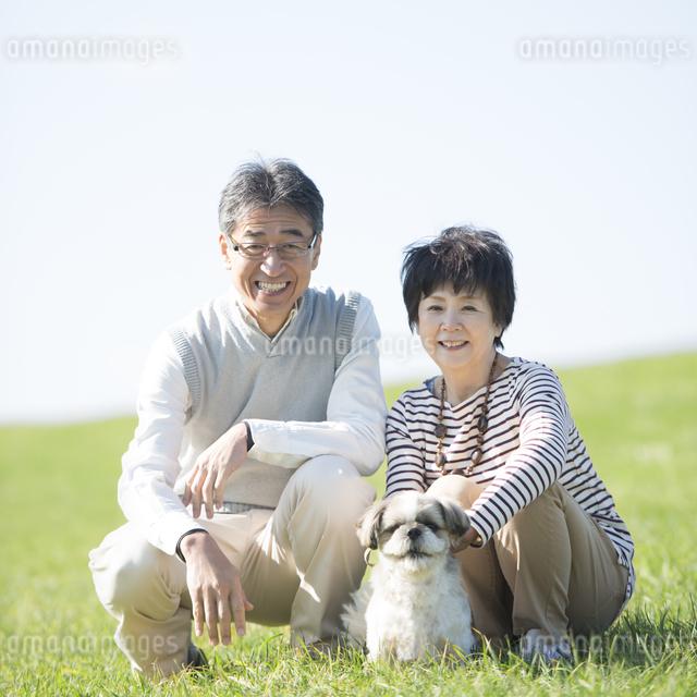 草原で微笑むシニア夫婦と犬の写真素材 [FYI04557195]