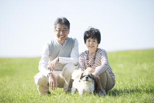 草原で微笑むシニア夫婦と犬の写真素材 [FYI04557196]