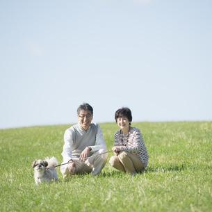 草原で微笑むシニア夫婦と犬の写真素材 [FYI04557223]