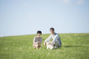 草原で微笑むシニア夫婦と犬の写真素材 [FYI04557225]