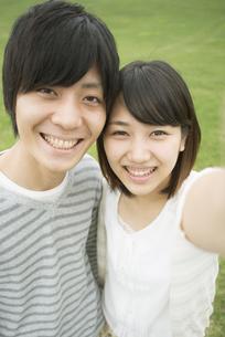 草原で自撮りをするカップルの写真素材 [FYI04557226]