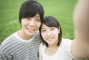 草原で自撮りをするカップルの写真素材 [FYI04557230]
