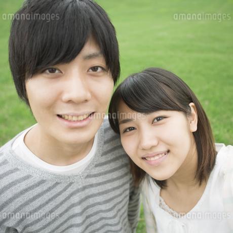 草原で微笑むカップルの写真素材 [FYI04557232]